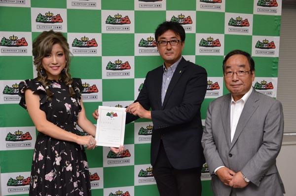 824富岡市長(右)の立ち会いの下、清水実行委員長(中)から委嘱状を受け取る石関さん