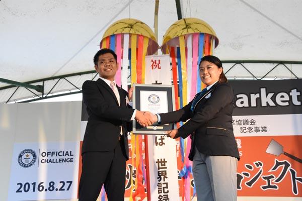 828ギネス世界記録に認定され、公式認定員と握手を交わす吉沢理事長(左)