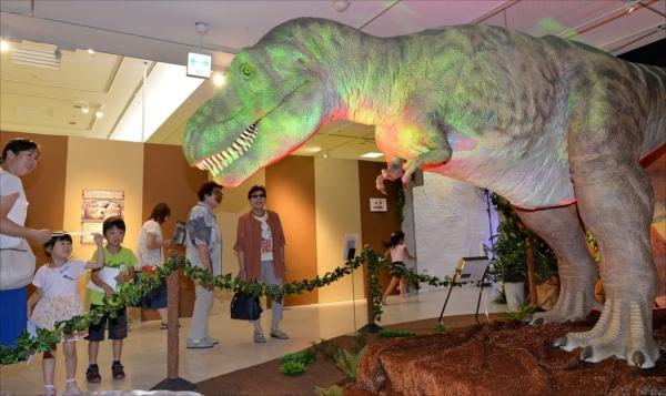 迫力満点の恐竜に見入る家族連れ=4日午後1時10分、宇都宮市宮園町、橋本裕太撮影