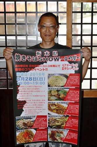 「焼きそばSHOW 夏の陣」のポスターを手にする実行委の山本さん