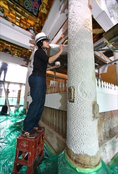 陽明門の逆柱に胡粉を塗る作業員=27日午前9時45分、日光市山内の日光東照宮