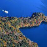 群青色の湖面に際立つ八丁出島の紅葉=26日午前9時、日光市中宮祠