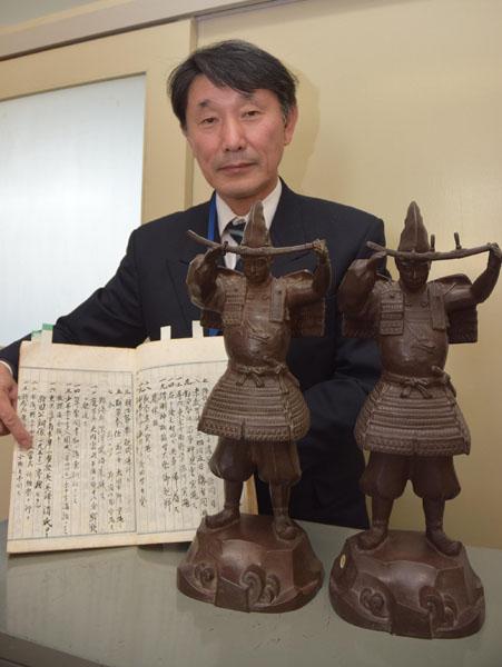 0211義貞像寄贈の記述がある沿革誌を示す木村校長。手前が三郷小の像(右)と附属小の像