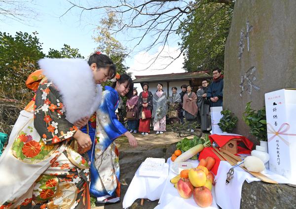 09碑の前に置かれた豆腐に針を刺し、和裁の上達と健康を願う生徒