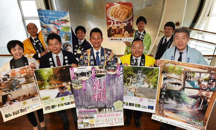 0309栃木の観光ポスターを掲げるキャラバンのメンバー