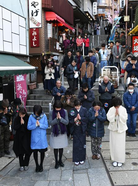 0312手を合わせ黙とうする女将や観光客ら=11日午後2時46分、渋川市の伊香保温泉石段街
