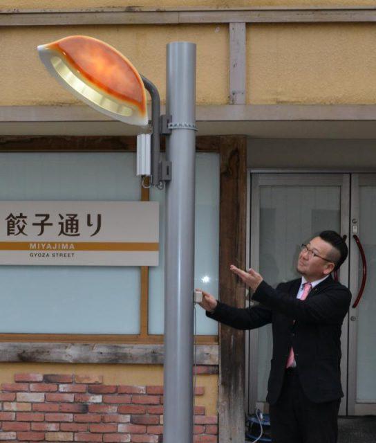 ギョーザ型の街灯を披露する宇都宮餃子会の鈴木章弘事務局長