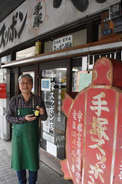 昔ながらの外観を保つ手塚スッポン店。手塚さんが手にしているのがオリジナルドリンク「タオ」