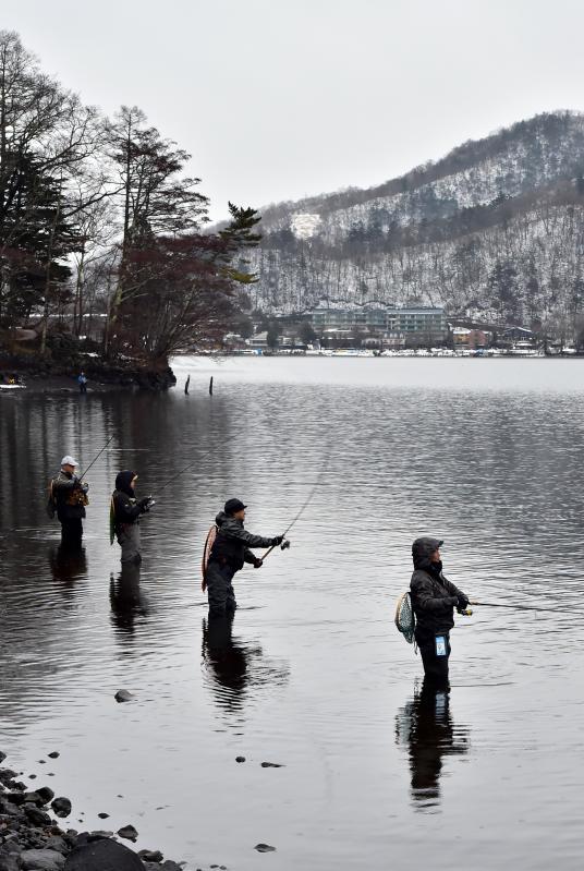 雪が残る中禅寺湖で釣りを楽しむ人たち